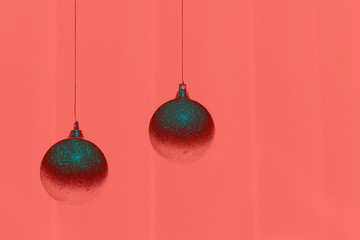 Two Christmas balls on background in color of living coral