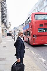 UK, London, senior businessman with luggage waiting at crosswalk