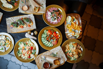 A set of juicy servings of steak, cheese platter, healthy vegetable platter, meat, sandwiches, fruits, carpaccio and tartar, nuggets, Caesar salad of french fries. View from above. Feast. Healthy food