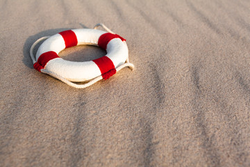 Beach Nostalgia -  Lifebelt and Sand Background / Nostalgic miniature white life buoy with rope and red stripes at wavy beach sand background (copy space)