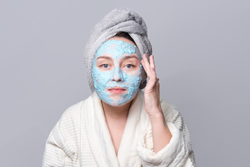 Woman applying facial clay mask at spa salon or at home, skincare theme. Face mask, spa beauty treatment with copy space on gray background.