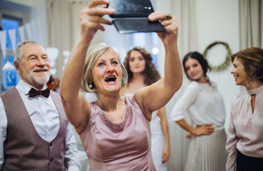 A senior woman with husband on wedding or birthday party, taking selfie with smartphone.