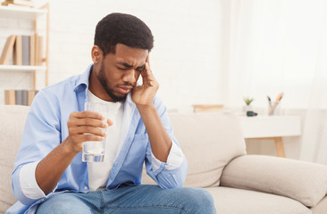 African-american man with headache taking pill at home