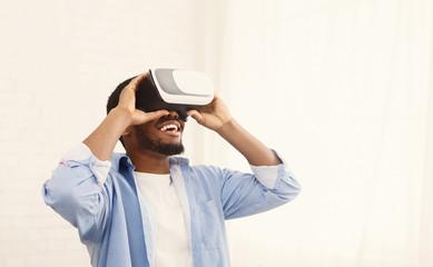 Joyful black man using VR headset at home