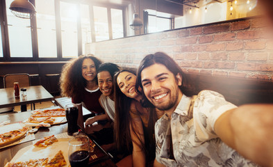 Group of multi-ethnic friends making selfie at restaurant