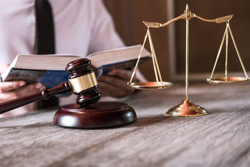 Male lawyer or judge working with Law books, gavel and balance, report the case on table in office, Law and justice concept