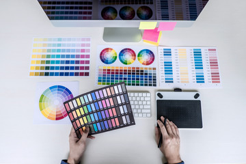 Male creative graphic designer working on color selection and color swatches, drawing on graphics tablet at workplace with work tools and accessories, top view workspace