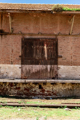 Sliding wooden door of a barn or deposit with a brick wall and old railways down with green grass