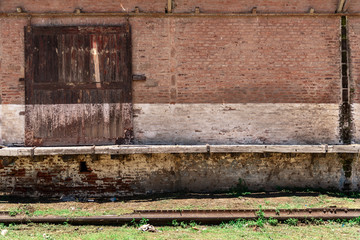 Sliding wooden door of a barn or deposit with a brick wall to write something and old railways down with green grass