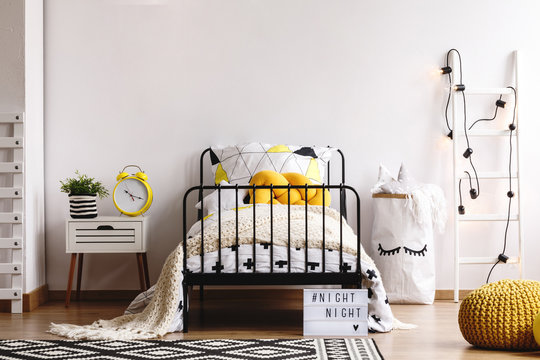 Yellow knit pillow on single metal bed with patterned duvet and white warm blanket in spacious bedroom interior with copy space on empty white wall