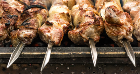 Close-up of hot roasted meat on metal skewers