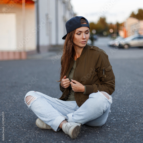 58936b628c Pretty cute young fashionable woman with long hair in a fashionable green  military jacket in stylish ripped blue jeans and white stylish sport  sneakers sits ...