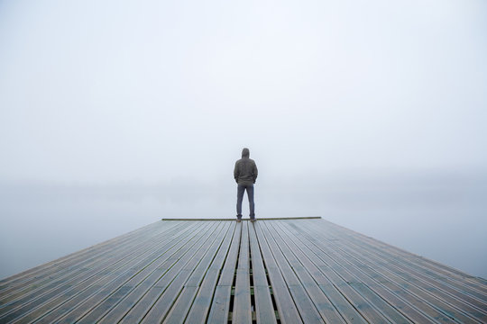 Young man standing alone on edge of footbridge and staring at lake. Mist over water. Foggy air. Early chilly morning in autumn. Beautiful freedom moment and peaceful atmosphere in nature. Back view.