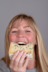 Blonde woman eating and enjoying a wedge of blue cheese