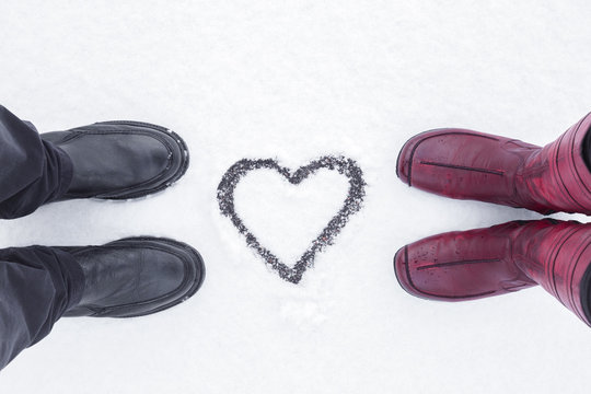 Young couple's boots standing opposite each other. Heart shape drawn on fresh, white snow in middle. Dating in winter day. Point of view shot.