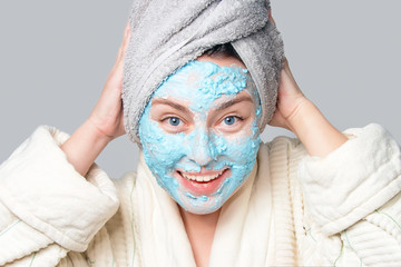 Woman with facial clay mask at spa salon or at home, skincare theme. Girl removes alginate cosmetic mask. Face mask, spa beauty treatment with copy space on gray background.
