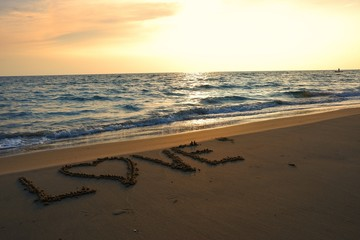 Valentines day concept, love heart shape handwriting on sand beach in sunrise and blue ocean.