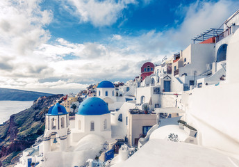 Churches in Oia, Santorini island in Greece, on a sunny day with dramatic sky. Scenic travel background.
