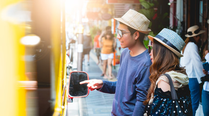A couple of blogger tourists from Southeast Asia. Visit Phuket in Thailand are Asking Route price from driver in the old town of Phuket during write travel reviews with sunlight in travel concept .