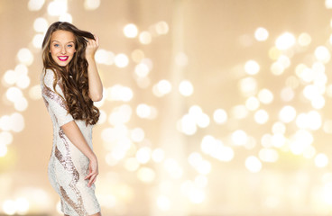 people, style, holidays, hairstyle and fashion concept - happy young woman or teen girl in fancy dress with sequins touching long wavy hair over festive lights background Wall mural
