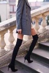 beautiful fashionable woman in gray coat and black knee high heel boots walking and posing outdoors