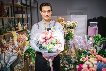 Obraz Handsome young male florist stand and look on camera. He hold bouquet of flowers in hands. Guy stand inside. He cheerful. - fototapety do salonu