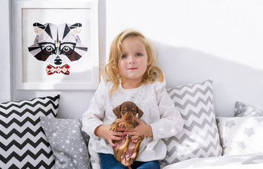Beautiful little girl posing with puppy in bedrooom.