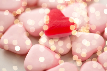valentines day, sweets and confectionery concept - close up of red and pink heart shaped candies over festive lights