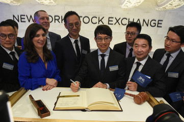 Cussion Kar Shun Pang, CEO of Tencent Music Entertainment and members of the company's leadership team sign the ceremonial book before the opening bell to celebrate company's IPO on the floor of the New York Stock Exchange (NYSE) in New York