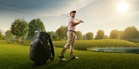 Male golf player on professional golf course. Smiling golfer walking on fairway with golf bag and club