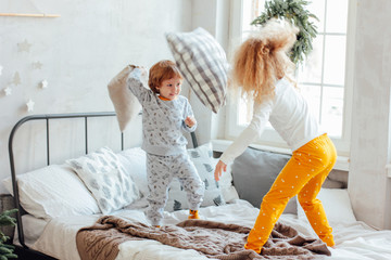 Brother and sister in pajamas playing with pillows on the bed