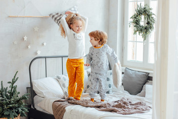 Brother and sister in pajamas playing with pillows on the bed, c
