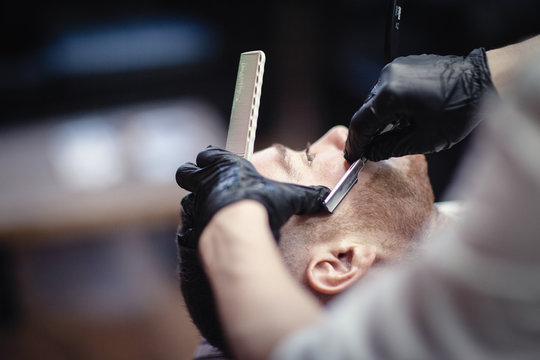 Hairdresser in black gloves shaves with a straight razor beard