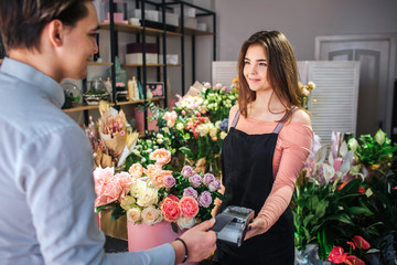 Picture of young female florist holding money therminal. She stand in front of customer. Young businessman pay for flowers.