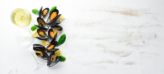 A bottle of white wine and mussels. Top view. Free space for your text. On the old background.