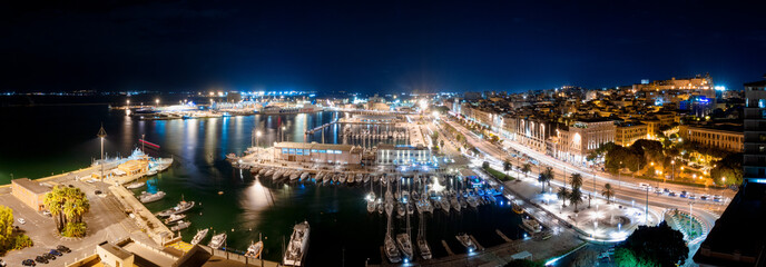 Panoramic view of Cagliari at night with harbor in foreground
