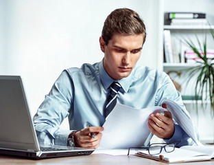 Serious businessman sitting at his desk reading a documents. Photo of successful man working in the office. Business concept