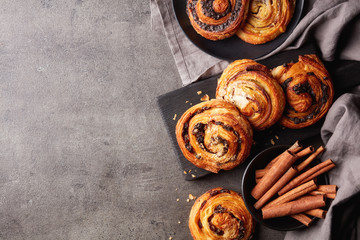 Sweet buns on black board isolated on stone table, from above