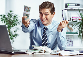 Successful businessman takes off his glasses and showing money. Photo of young man working in the office. Business concept