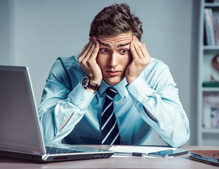 Young businessman with pain in his temples. Photo of man suffering from stress or a headache grimacing in pain. Business concept