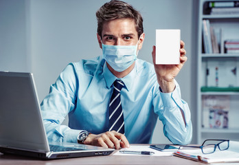 Healthy worker at the office holding white box of medicine. Photo of man wearing protective mask against infectious diseases and flu. Business and health care concept.