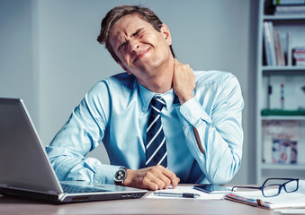 Employee suffers from severe pain in neck. Photo of man working in the office. Medical concept.