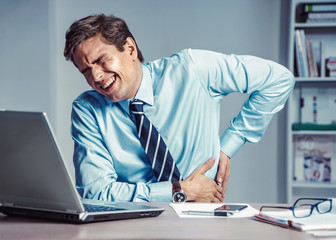 Employee suffers from severe pain in back. Photo of man working in the office. Medical concept.