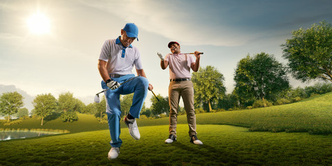 Male golf players on professional golf course. Happy player emotionally rejoices victory. Angry opponent sad about losing and broke his golf club on knee Wall mural