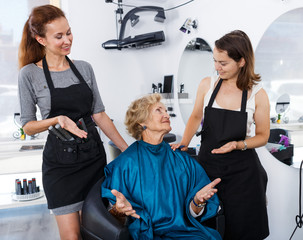 Hairstylists and satisfied female customer after haircut