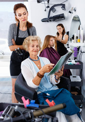 Young woman hairdresser in hair salon helping to senior woman ch