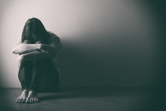 Teenager girl with depression sitting alone on the floor in the dark room. . Black and white photo