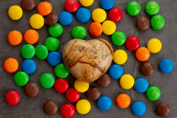 The stone heart is among the many scattered chocolate drops in bright glazes of red, yellow, blue, green, orange and brown colors on a gray granite background. Background for festive gift flyer.