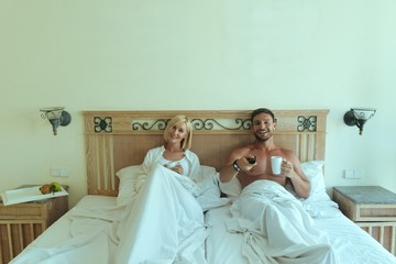 handsome man and beautiful blonde woman lying in bed together having fun watching tv in bedroom, Attractive husband and wife relaxing after sex in the morning, drinking coffee smiling watching comedy
