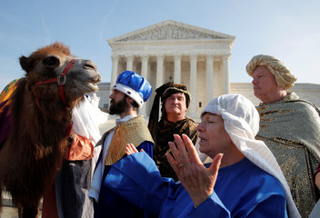"A woman prays next to actors dressed as the ""Three Wise Men"" to replicate the nativity scene in front of the Supreme Court during a event organized by the religious group ""Faith and Liberty"" to exercise First Amendment Rights and support of religious freed"